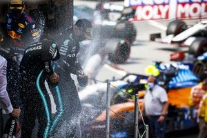 Lewis Hamilton, Mercedes, 1st position, Max Verstappen, Red Bull Racing, 2nd position, and Valtteri Bottas, Mercedes, 3rd position, spray Champagne on the podium