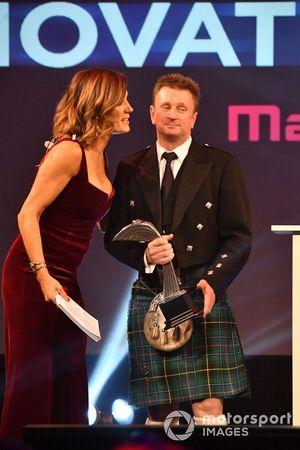 Allan McNish op het podium met Natalie Pinkham, Sky TV, om de Pioneering and Innovation Award uit te reiken
