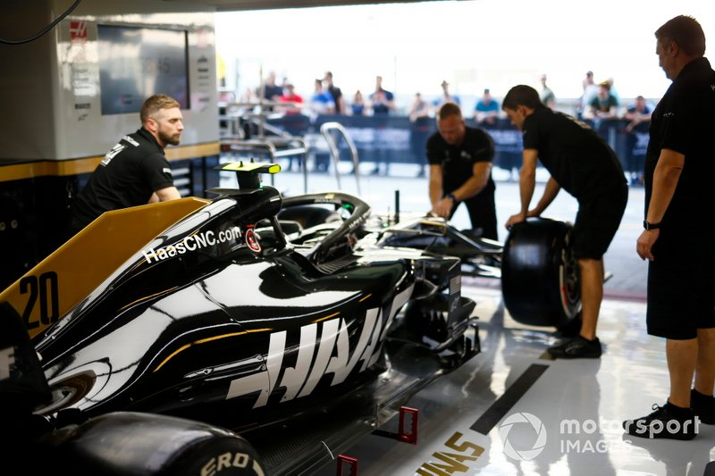 Mechanics work on the Kevin Magnussen Haas F1 Team VF-19 in the team's pit garage