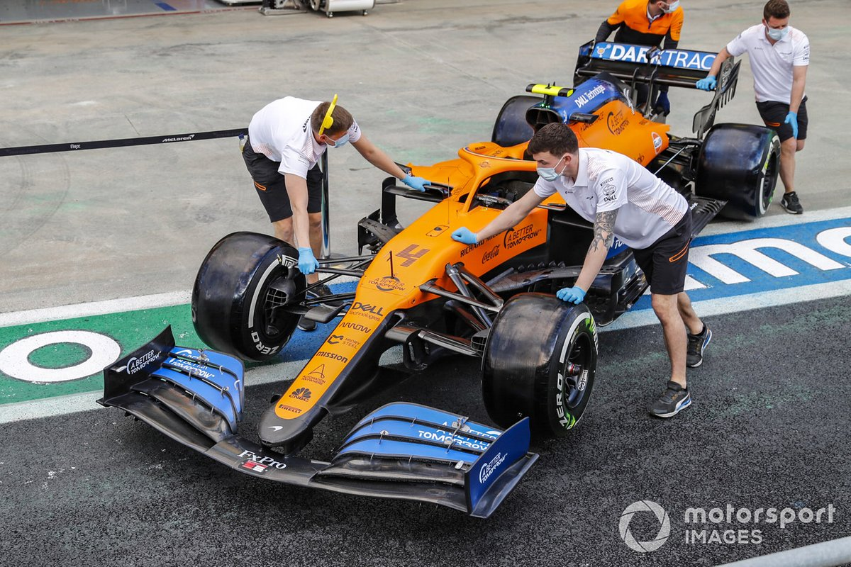 McLaren personnel wheel a car along the pitlane