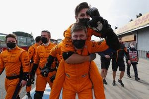 McLaren mechanics celebrate in the pitlane