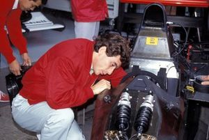 Ayrton Senna checks on something in the cockpit of his McLaren MP4-6