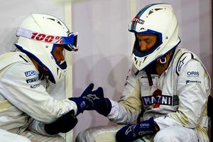 Williams pit crew members pass the time in the pit lane
