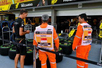 Renault mechanic and scrutineers outside Renault F1 Team garage
