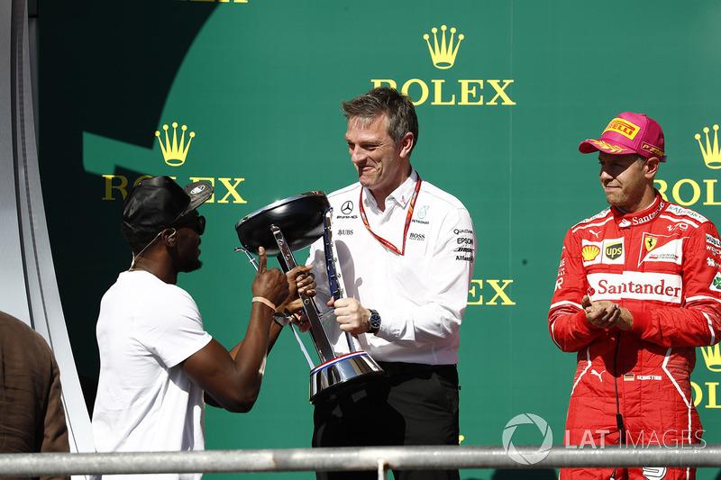 Usain Bolt entrega a James Allison, director técnico de Mercedes AMG F1, el trofeo de constructores