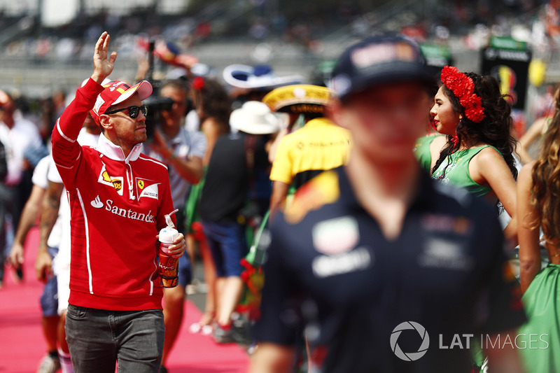 Sebastian Vettel, Ferrari, waves to the crowd, behind Max Verstappen, Red Bull Racing