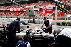 Robert Kubica, Williams, is attended to by mechanics in the pit lane