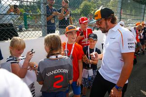 Fernando Alonso, McLaren, signs autographs for young fans