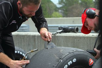 Team Penske crewmember examines tires