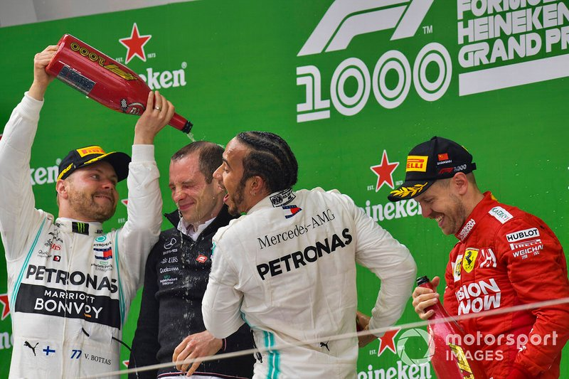 Valtteri Bottas, Mercedes AMG F1, 2nd position, the Mercedes Constructors trophy delegate, Lewis Hamilton, Mercedes AMG F1, 1st position, and Sebastian Vettel, Ferrari, 3rd position, on the dium