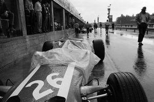 Joakim Bonnier's Cooper T81 Maserati protected by a tarp in the pit lane