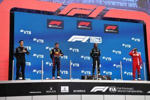 The Mercedes trophy delegate, Max Verstappen, Red Bull Racing, 2nd position, Lewis Hamilton, Mercedes, 1st position, and Carlos Sainz Jr., Ferrari, 3rd position, on the podium