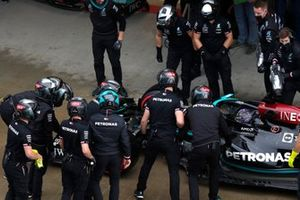The Mercedes pit crew inspect the damaged front wing on the car of Lewis Hamilton, Mercedes W12