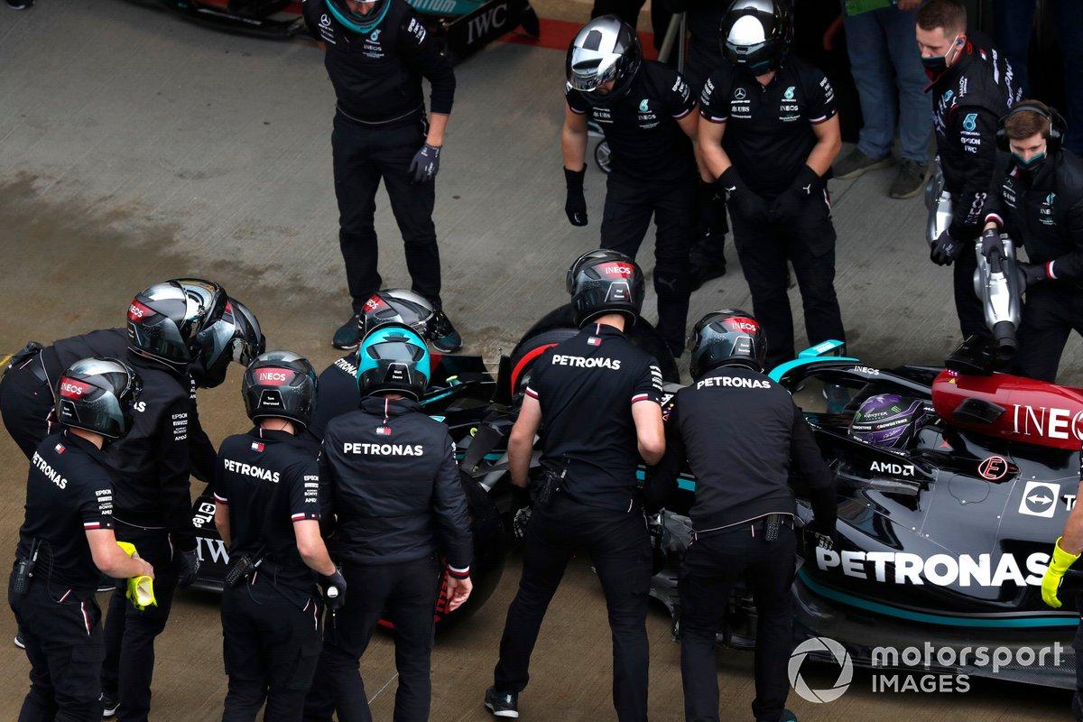 El equipo de boxes de Mercedes inspecciona el alerón delantero dañado del coche de Lewis Hamilton, Mercedes W12