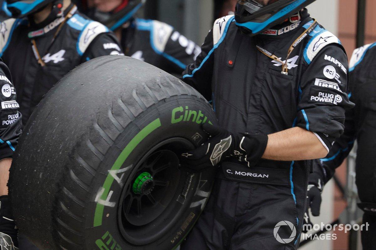Un miembro del equipo de boxes de Alpine F1 con un neumático intermedio desgastado