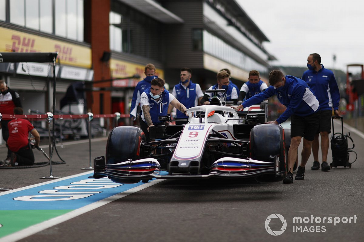Los mecánicos de Haas F1 empujan el coche de Nikita Mazepin, Haas VF-21 por el pitlane