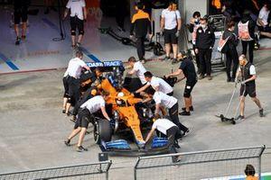 Lando Norris, McLaren MCL35M, wordt teruggebracht in de garage