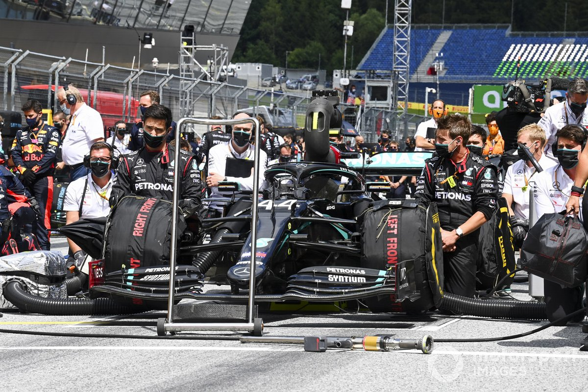 Mecánicos de Mercedes se arrodillan