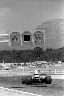 Un McLaren M23 pasa por debajo de un sistema de pórtico de luces de advertencia