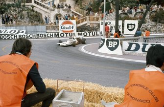 Marshals watch Denny Hulme, McLaren M19C Ford negotiate the hairpin
