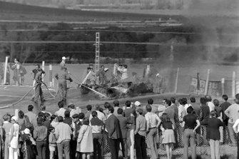 Los aficionados de pie en la valla mientras los oficiales trabajan para extinguir un coche en llamas