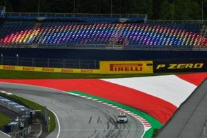 The Mercedes safety car drivers past an empty grandstand illuminated by multi-coloured lighting