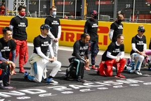 The drivers including Lewis Hamilton, Mercedes-AMG F1, both stand and take a knee in support of the End Racism campaign prior to the start