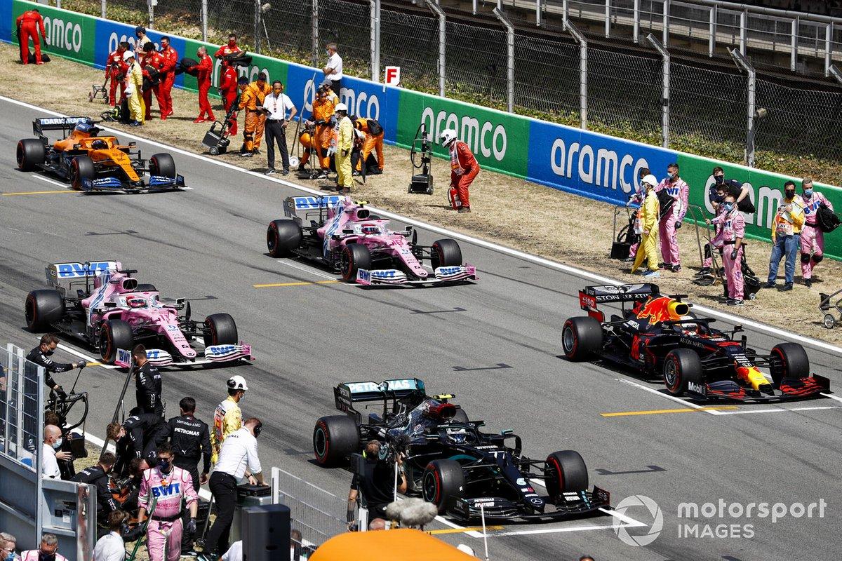 Los mecánicos despejan la parrilla mientras Valtteri Bottas, Mercedes F1 W11 EQ Performance, Max Verstappen, Red Bull Racing RB16, Sergio Pérez, Racing Point RP20, Lance Stroll, Racing Point RP20, Carlos Sainz Jr., McLaren MCL35, se preparan para iniciar la vuelta de formación