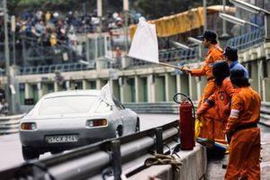Los oficiales de pista ondean una bandera blanca mientras el pace car pasa