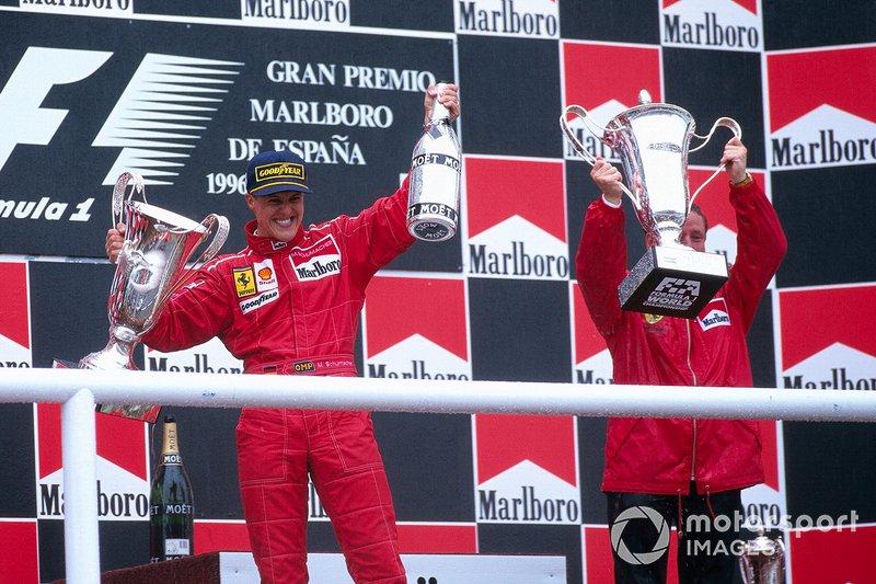 Michael Schumacher fête sa première victoire pour Ferrari sur le podium avec Jean Todt