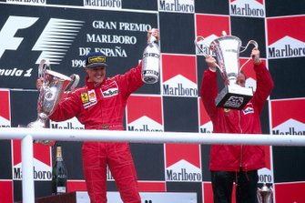 Michael Schumacher celebrates his first victory for Ferrari on the podium with team boss Jean Todt