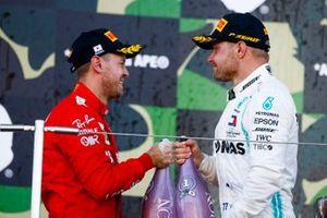 Race winner Valtteri Bottas, Mercedes AMG F1 and Sebastian Vettel, Ferrari celebrate on the podium with thee champagne