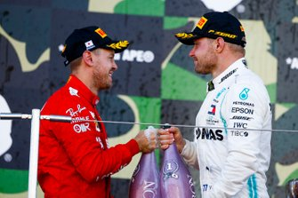 Race winner Valtteri Bottas, Mercedes AMG F1 and Sebastian Vettel, Ferrari celebrate on the podium with thee champagne