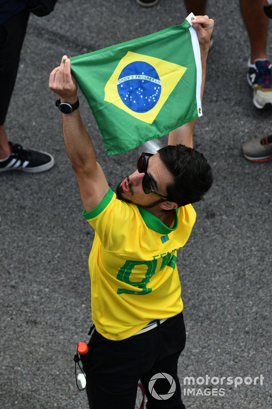 A fan celebrates with the national flag after the race