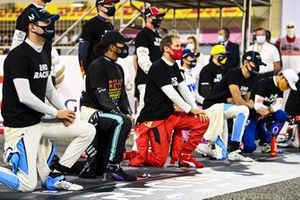 The drivers stand and kneel in support of the End Racism campaign prior to the start