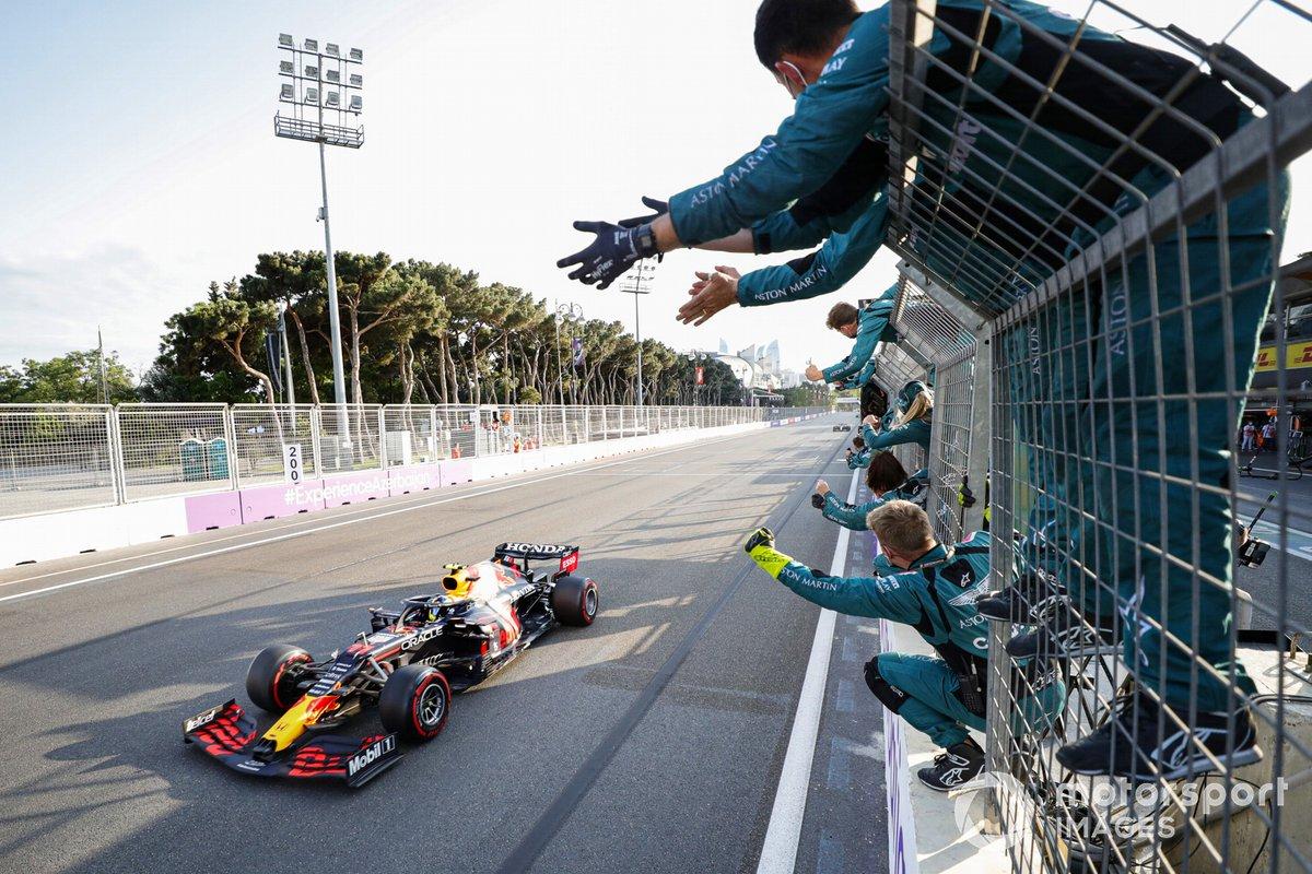 Sergio Pérez, Red Bull Racing RB16B, 1ª posición, es animado en la línea de meta por miembros del equipo Aston Martin
