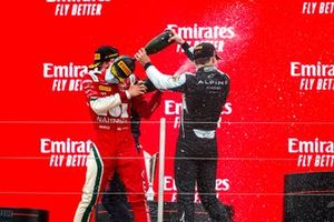 Arthur Leclerc, Prema Racing, 1st position, and Victor Martins, MP Motorsport, 3rd position, celebrate on the podium with Champagne