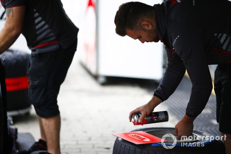 Un membre de Haas peint des pneus