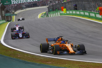 Fernando Alonso, McLaren MCL33, leads Brendon Hartley, Toro Rosso STR13, and Esteban Ocon, Racing Point Force India VJM11