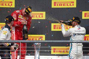 Max Verstappen, Red Bull Racing, 2° classificato, e Lewis Hamilton, Mercedes AMG F1, 3° classificato, spruzzano Kimi Raikkonen, Ferrari, 1st position, con lo Champagne, sul podio