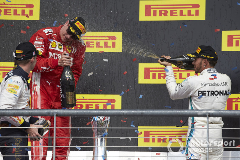 Max Verstappen, Red Bull Racing, 2nd position, and Lewis Hamilton, Mercedes AMG F1, 3rd position, spray Kimi Raikkonen, Ferrari, 1st position, with Champagne on the podium