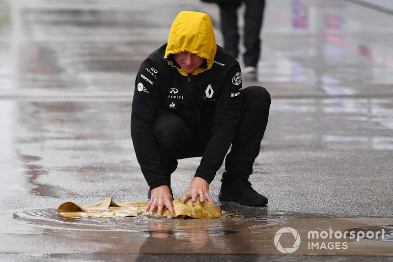 Un meccanico Renault Sport F1 Team con un panno di camoscio, asciuga la piazzola box