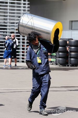 A man carrying a cylinder in the paddock