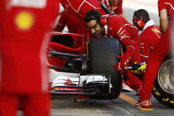 A mechanic changes a front wheel during a pit stop on the Sebastian Vettel Ferrari SF70H