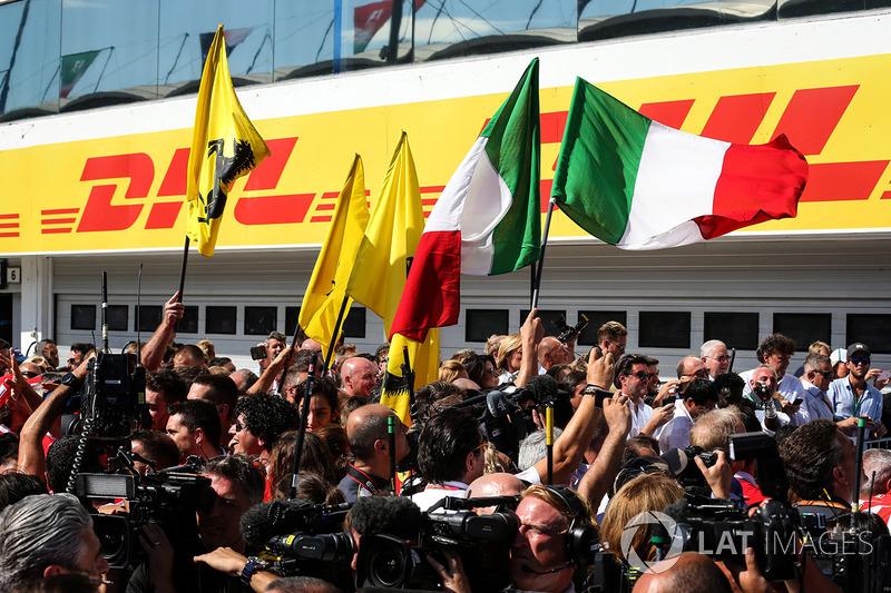 Il team Ferrari festeggia con le bandiere nel parco chiuso