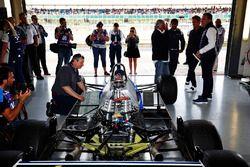 A six-wheeled Williams FW08 is prepped, as Karun Chandhok, Keke Rosberg and Nico Rosberg watch on