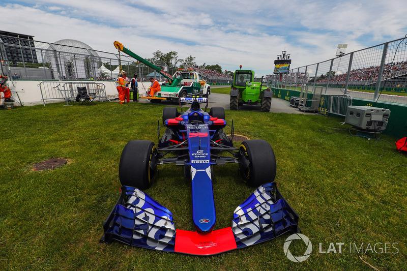 El coche de Carlos Sainz Jr., Scuderia Toro Rosso STR12 es quitado por los oficiales de pista