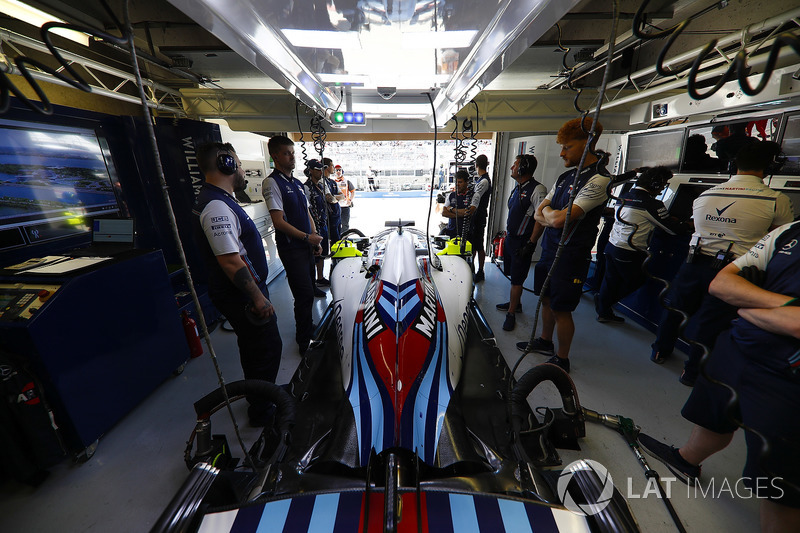Mechanics attend the Lance Stroll Williams FW41 in the team's garage