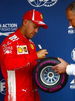Sebastian Vettel, Ferrari, signs the Pirelli Pole Position award