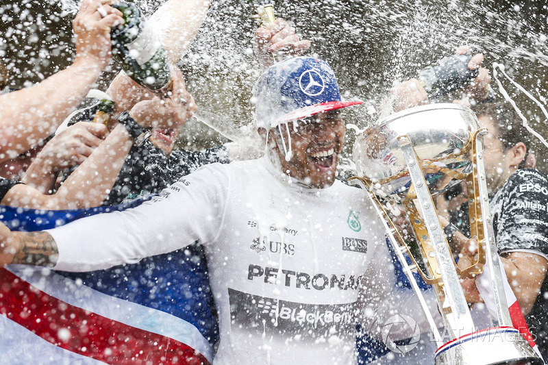 Podium: race winner Lewis Hamilton, Mercedes gets a Champagne soaking from his team after securing a third World Drivers Championship victory